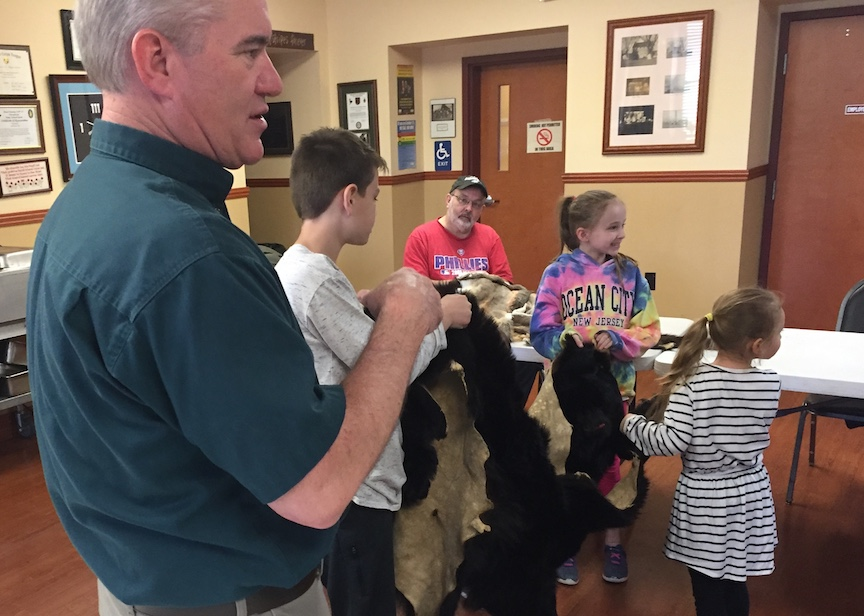 Children enjoy holding bear skin.